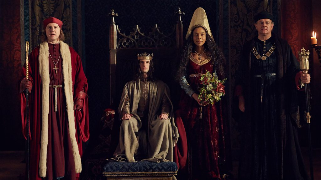 Samuel West (como Bishop de Winchester), Tom Sturridge (como Henry VI), Sophie Okonedo (como Margaret de Anjou) e Hugh Bonneville (somo Gloucester) em uma foto promocional da série  The Hollow Crown: A Guerra das Rosas.  Foto por Robert Viglasky via PBS