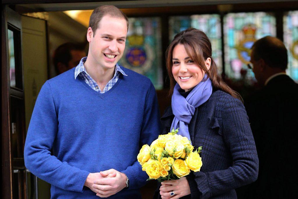 Kate está segurando um buquê de rosas e está usando um casaco e um cachecol. William está a direita dela, usando um suéter. Ambos estão em frente a porta do hospital.