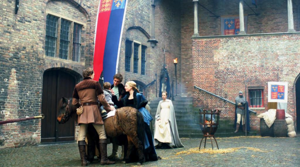 Imagem de Edward IV (Max Irons), Elizabeth Woodville (Rebecca Ferguson) e Anthony Woodville (Ben Lamb)  brincando com com o Príncipe Edward (montado em um pónei)