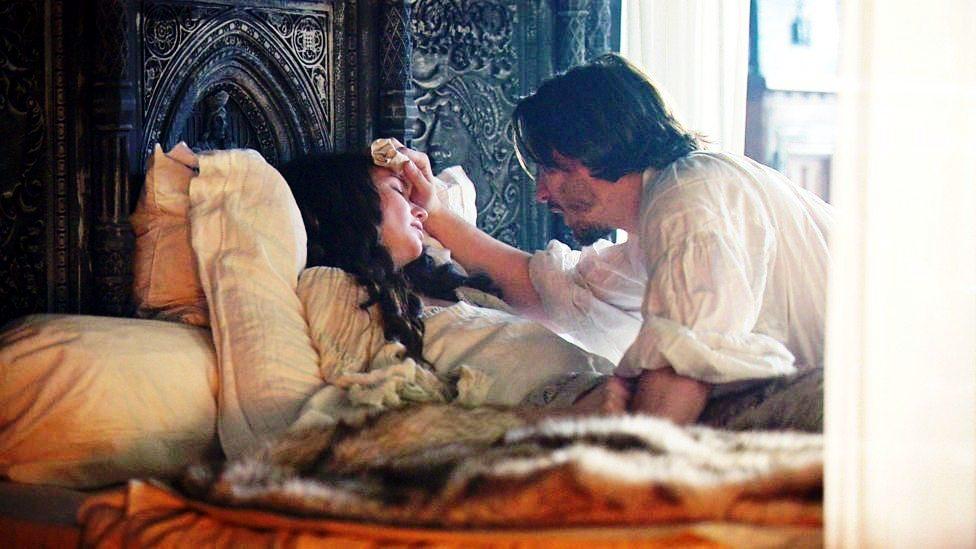 Isabel está doente na cama e George está secando o rosto dela.