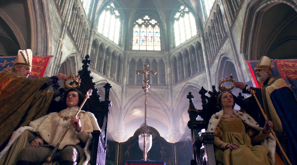 Imagem dos arcebispos aproximando as coroas das cabeça do rei e da rainha. O plano evidência a arquitetura da abadia e o casal sentado em seus respectivos tronos.