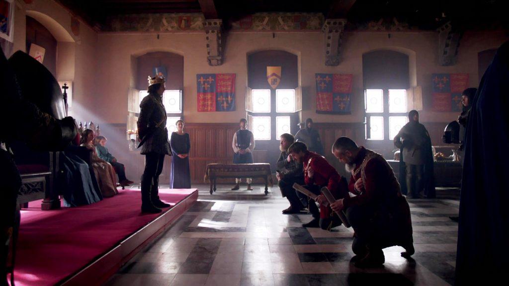Richard III de pé em frente ao trono, enquanto Sir Robert, O Duque de Buckingham e Thomas Stanley estão ajoelhados na frente dele aceitando os novos cargos