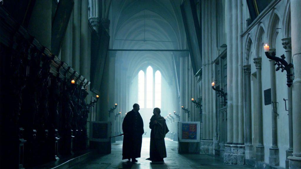 Elizabeth e Dr Lewis estão dentro da Abadia de Westminster, a igreja está no primeiro plano e os dois ao fundo, conversando em pé.