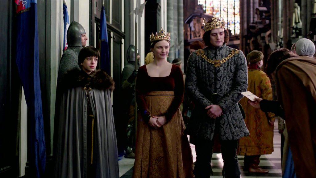 Edward, Anne e Richard estão em pé, o rei e a rainha usando coroas enquanto há uma fila de pessoas para cumprimentá-los. Um homem está estendendo um envelope para Richard.