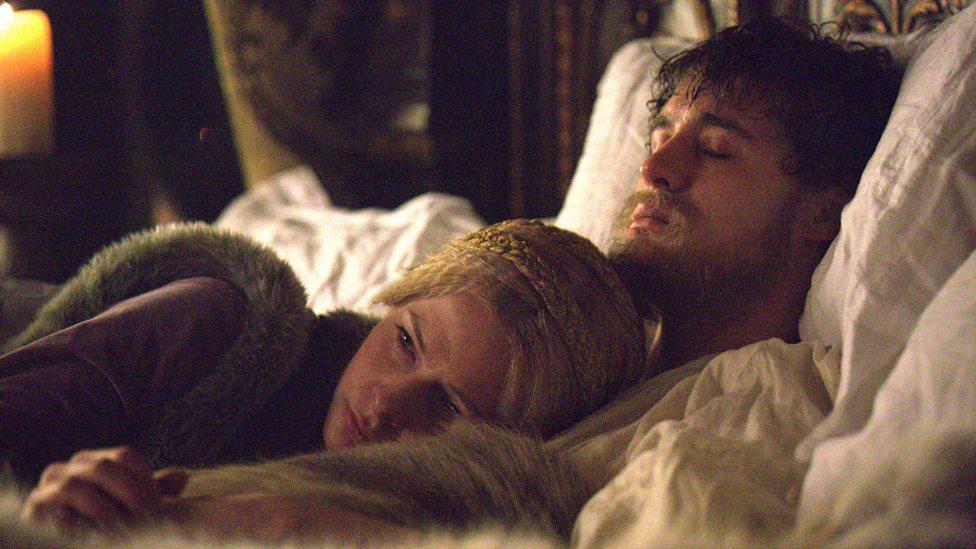 Imagem de Elizabeth abraçando o marido deitado no leito de morte.