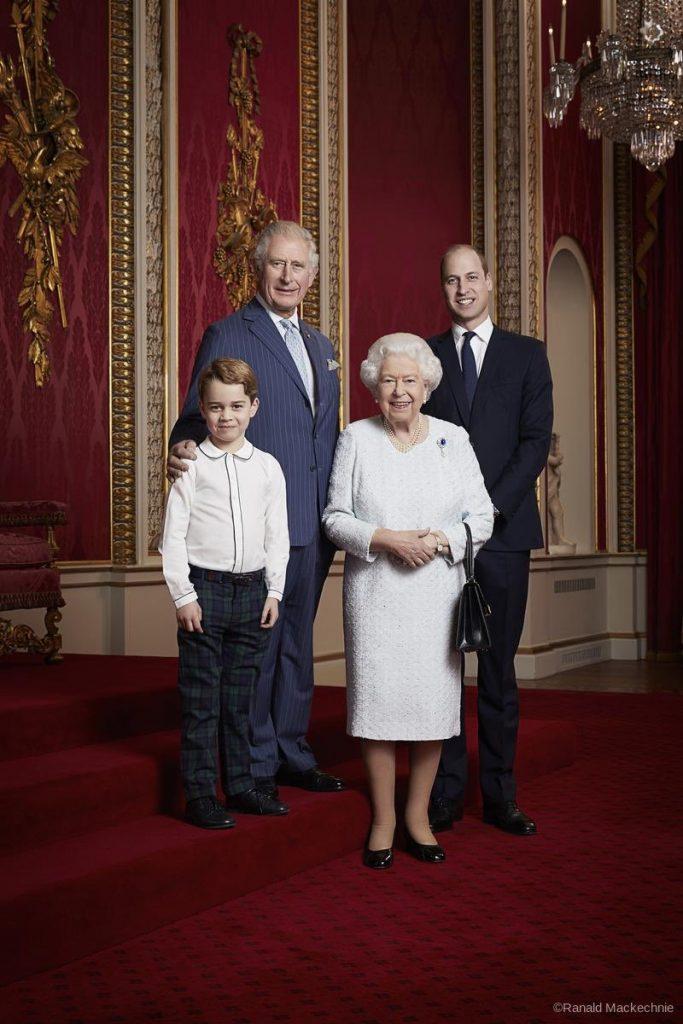 Todos estão em frente a uma parede vermelha, na Sala do Trono do Palácio de Buckingham. George está vestindo um camisa branca de manga comprinha e calça xadrez verde e azul. Charles veste um terno riscado azul, camisa branca e gravata azul clara, A rainha veste um vestido bordado branco de mangas compridas, está segurando uma bolsa preta e veste um broche de safira. William está de terno azul escuro, camisa branca e gravata azul.  Todos estão sorrindo para a foto.