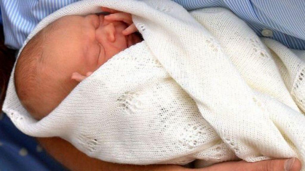 Príncipe George está enrolado em uma mantinha de fios grossos. Ele está dormindo com as mãozinhas cobrindo parte das bochechas.