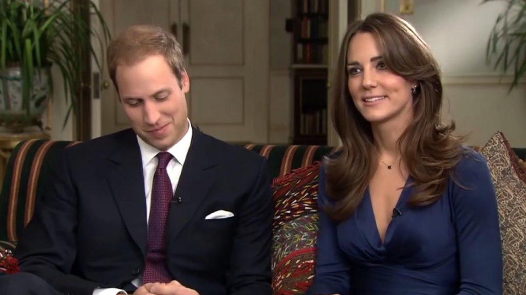 William e Kate estão sentados em um sofá. William está sorrindo timidamente para baixo enquanto Kate conversa com o jornalista.