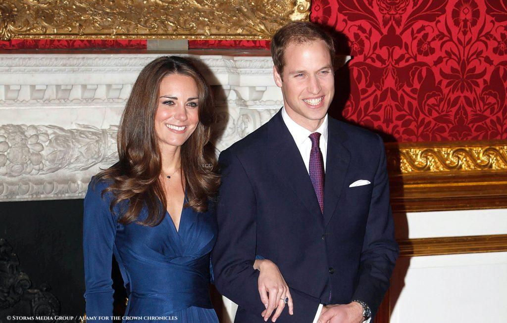 William e Kate estão em frente a uma parede com vários quadros históricos no Palácio de St James.