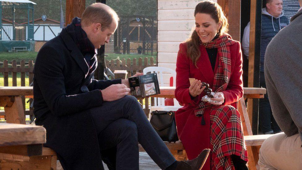 William e Kate com os presentes nas mãos. Eles usam a mesma roupa da foto anterior e estão no mesmo lugar. Kate está sorrindo olhando para William e William está olhando para o presente, surpreso.