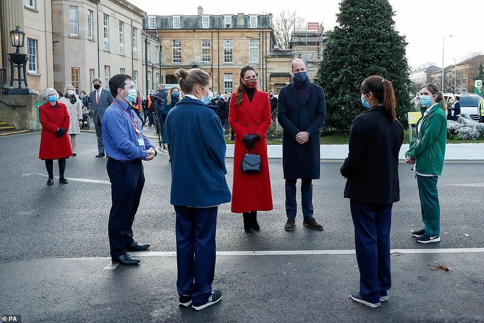 William e Kate estão com as mesmas roupas dos compromissos anteriores. Os funcionários estão em volta dele, do lado de fora do hospital.