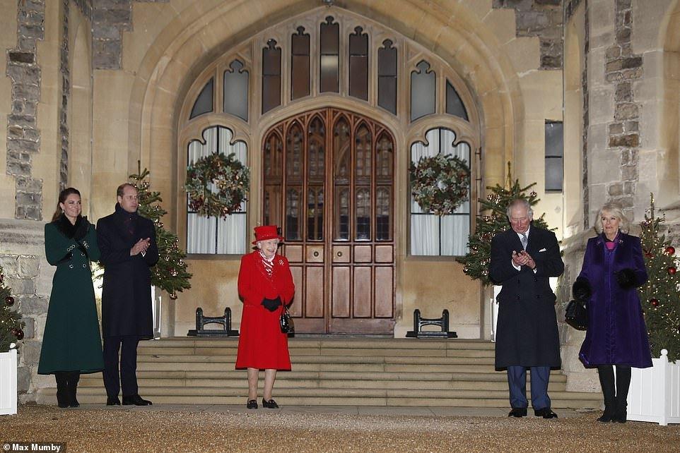 Kate veste um longo casaco verde com detalhes em preto e botas pretas, William veste um casaco azul e cachecol, a rainha veste um longo casaco vermelho, Charles leste um longo casaco azul com um terno azul por baixo e Camila veste um casaco roxo e botas pretas. Eles estão em frente a escadaria em uma das entradas do castelo de Windsor.