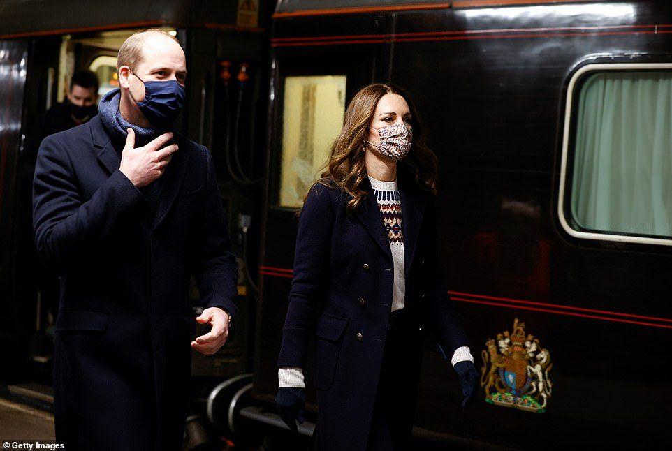 William e Kate estão ao lado do trem. Eles trocaram de roupa. Kate agora veste um casaco azul curto com botões dourados, luvas azuis e um suéter branco com bordados. William veste um azul da mesma cor e um cachecol azul. Ambos usam máscaras.