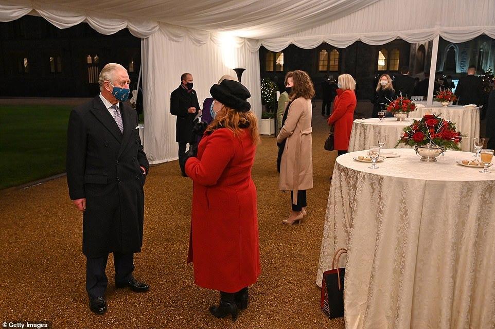 Charles e Camilla conversam com voluntários embaixo de uma tenda, com distanciamento social.
