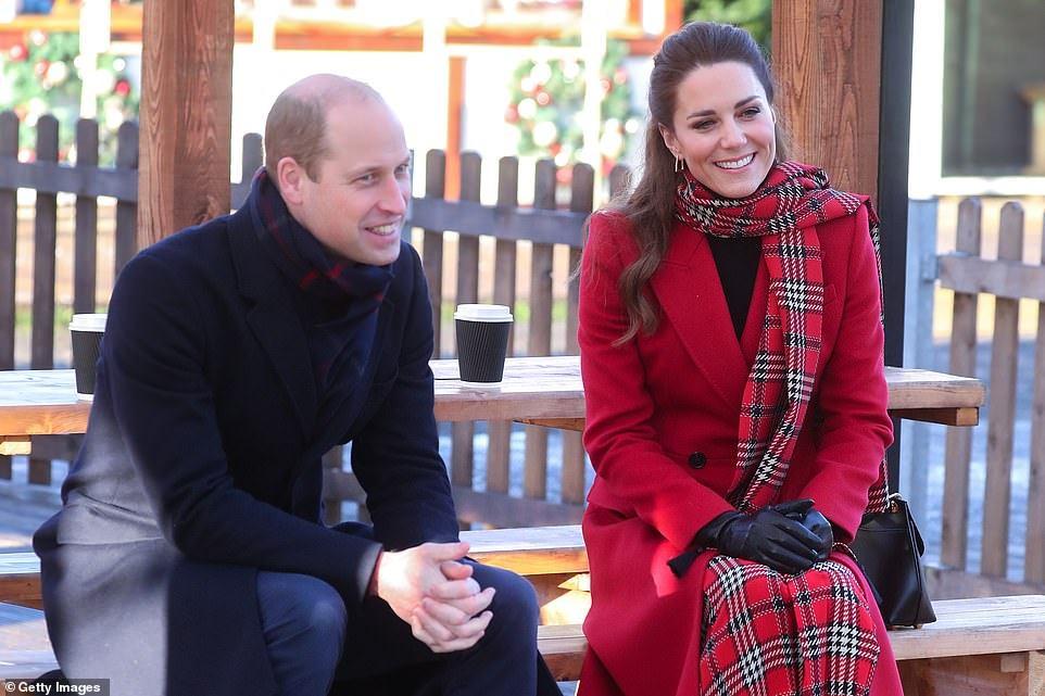 William e Kate estão sentados em um banco de madeira. Ambos estão sorrindo.  William veste um casaco azul escuro, calça jeans e cachecol xadrez azul e vermelho. Kate veste um longo casaco vermelho, um longo cachecol  xadrez vermelho, branco preto, calça e luva. O cabelo dela está meio preso.